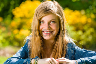 Smiling teenage girl looking at camera outdoors