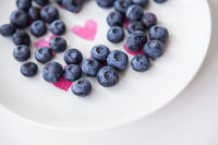 Delicious blueberries lie on a plate with a heart inside. Delicious and healthy food.