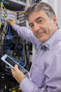 Man smiling while doing server maintenance with tablet