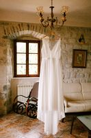Budva, Montenegro - 21 august 2020: Wedding attire of the bride on a wooden hanger on a chandelier in a room with a sofa and a rocking chair.