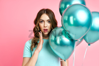 Portrait of pretty amazed woman with balloons on pink background