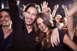Portrait of cheerful young friends enjoying at nightclub
