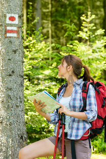 Female hiker checking the map and blaze