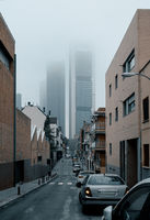 Urban road leading to four towers business area skyscrapers during misty weather. Madrid, Spain