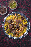 Traditional fried Arabic chicken majboos with chicken leg and jeweled rice served as top view in a rustic oriental tray