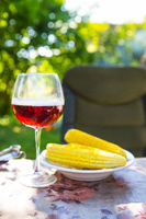 A glass of dark beer in a glass along with a plate of boiled corn, standing on the table. Summer picnic, beautiful sunshine.