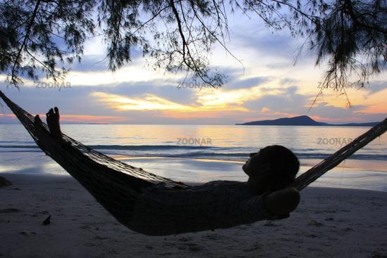 Young woman enjoying sunrise at Koh Rong island, C