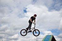 Belarus, Gomel, June 24, 2018. Central park. A teenager on an extreme bike performs a complicated trick.