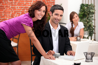 Woman leaning over a man in a restaurant with other diners in the background