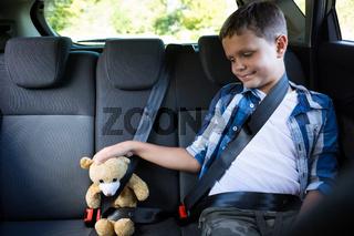 Teenage boy sitting with teddy bear in the back seat of car