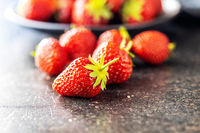 Whole ripe red strawberries on kitchen table.