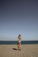 Back shot of blonde long-haired young woman walking on the beach in sunny day.