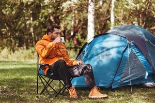 man drinking tea at tent camp