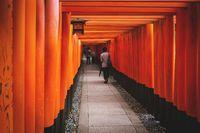 Tourists walking and making selfies in tunnel of torii gates at Fishimi Inari Taisha shrine, Japan
