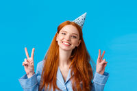 Happy cheerful redhead woman in birthday cap, tilt head and smiling upbeat, celebrating b-day, showing peace sign delighted, having sleepover party with friends, blue background