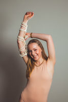 Fashion girl with rope strap on her hand at grey background