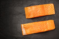 Two slices of salmon with on a black background with copy space, overhead photo