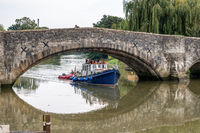 AYLESFORD, KENT, UK - SEPTEMBER 6 : View of a boat under the 14th century bridge at Aylesford on September 6, 2021. Three unidentified people