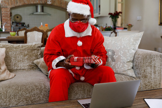 Senior african american man wearing a costume of santa claus and red face mask