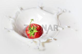 Strawberry dropped into milk with splash