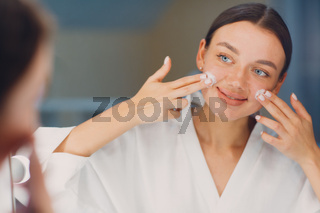 Young woman applying cosmetic white cream on her face at mirror