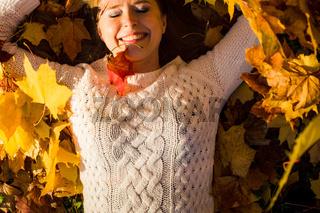 Woman laying in maple leaves in the park.