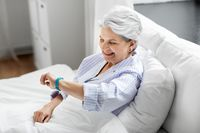 happy old woman with health tracker sitting in bed