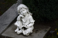 Sitting child with book in white marble