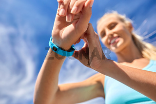 smiling young woman with fitness tracker outdoors