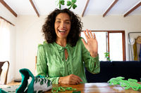 Caucasian woman dressed in green with shamrock deely boppers for st patrick's day waving during vide