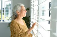 Smiling caucasian senior woman standing at window, looking into distance
