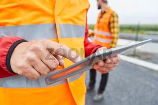 Bauarbeiter mit Hand am Touchscreen eines Tablet