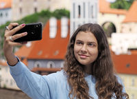 Young girl takes a selfie photo on the background of the historic town