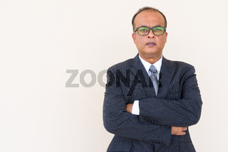 Portrait of Indian businessman with arms crossed against plain wall outdoors