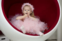 Two-year-old child. A smart little girl in a pink fluffy dress sits on a red chair.