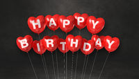 Red happy birthday heart shape air balloons on a black background scene. Horizontal Banner