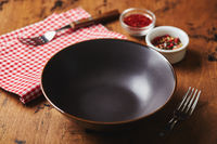 Empty dark bowl with fork, napkin and spices on wooden background