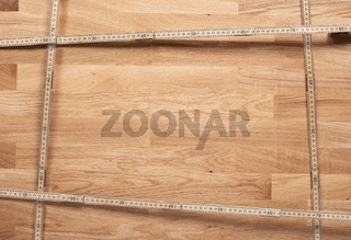 Wooden background with a frame of folding rulers