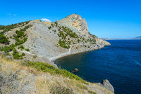 Summer mountain seascape-view of a rocky promontory overgrown with green bushes against the background of the sea going to the horizon and the blue sky on a sunny day