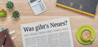 A newspaper on a desk with the headline Whats new in german - Was gibts Neues
