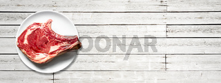 Beef prime rib and plate isolated on white wooden background. Horizontal banner