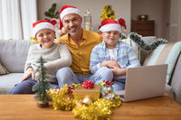 Portrait of caucasian father and two sons smiling while sitting at home during christmas
