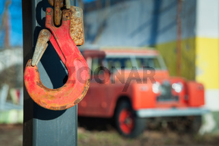 Red crane hook with oldtimer offroad vehicle in the blurry back