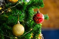 Composition of christmas tree with red and gold baubles on blurred background