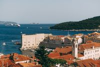 The old port harbor is porporela, near the walls of the old town of Dubrovnik, Croatia. View of the fort on the wall, Lokrum island and moored boats near the city walls.