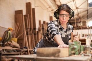 Schreiner Azubi mit Gehörschutz beim Holz hobeln