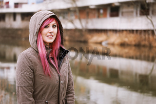 pierced young woman with pink hair and hooded parka standing by river