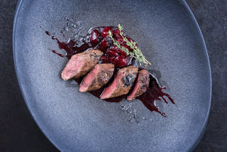Modern style traditional wild hare back filet braised with wild berries and cherry relish souse served as top view on Nordic design plate with copy space