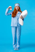 Sister telling time to bed, set alarm to wake up morning college lecture. Full-length vertical shot cute redhead feminine girl in pyjama and sleep mask, holding pillow and clock, smiling camera
