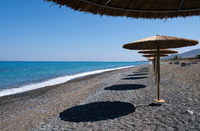 Tropical beach umbrellas providing sunshade for swimmers at an empty beach. Summer vacations.